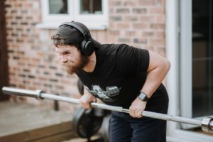strong bearded man lifting heavy barbell